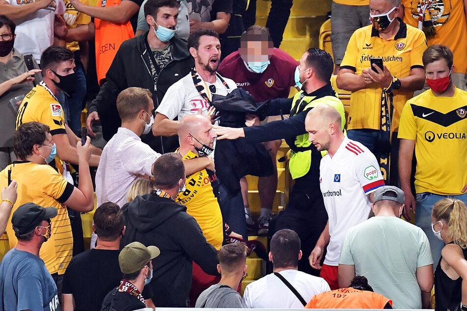 Toni Leistner (r., 30, weißes Trikot) wird von einem Ordner vom Dynamo-Fan (rotes Jersey), der ihn beleidigt haben soll, getrennt.