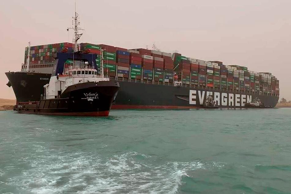 """Ein Schlepper versucht, die """"Ever Given"""" aus ihrer misslichen Lage im Suezkanal zu befreien."""