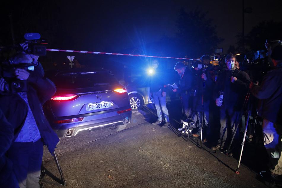 Ein Polizeiauto fährt vorbei an Journalisten am Tatort nach der brutalen Messerattacke.