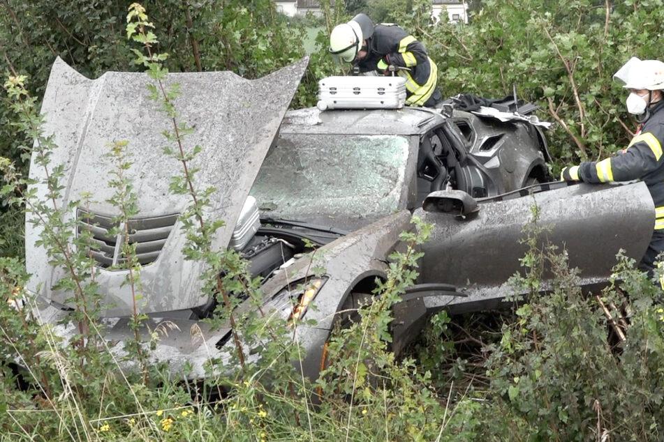 Das Bild zeigt das Wrack des Sportwagens in der Böschung neben der A67.
