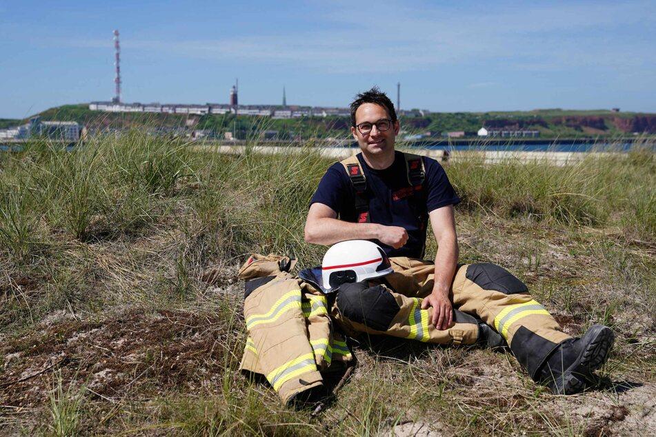 Felix Vorndran von der Freiwilligen Feuerwehr Bergisch-Gladbach sitzt an der Feuerwehrwache während seines Dünendienstes auf der Düne der Hochseeinsel Helgoland.