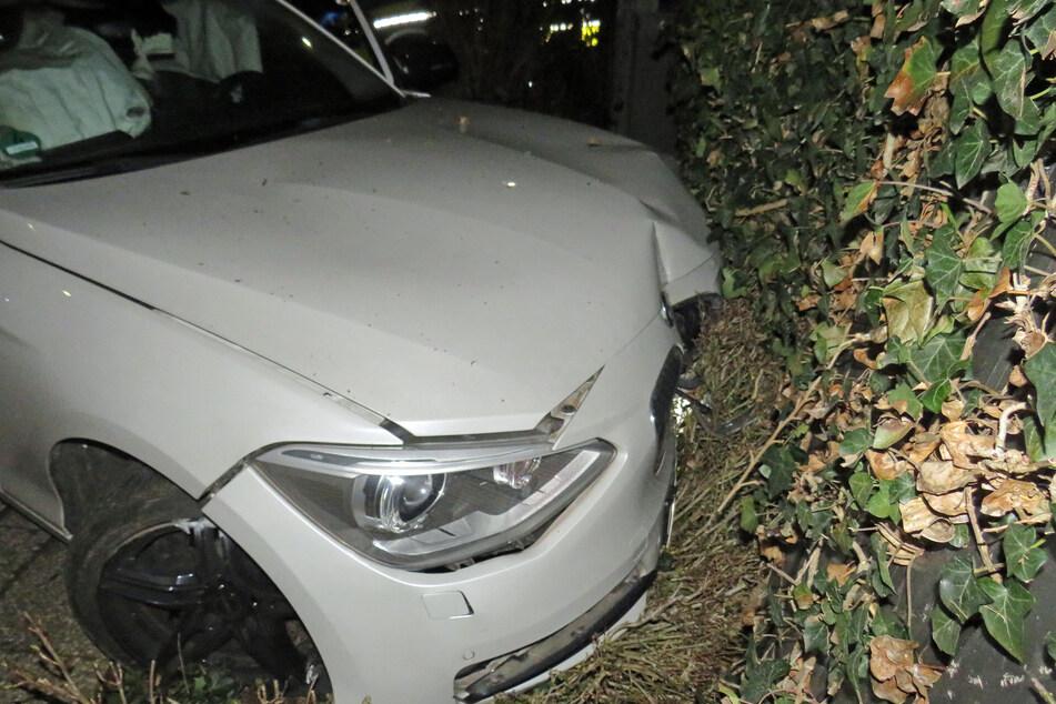 Der weiße BMW ist frontal mit einer getarnten Mülltonnenbox zusammengestoßen.