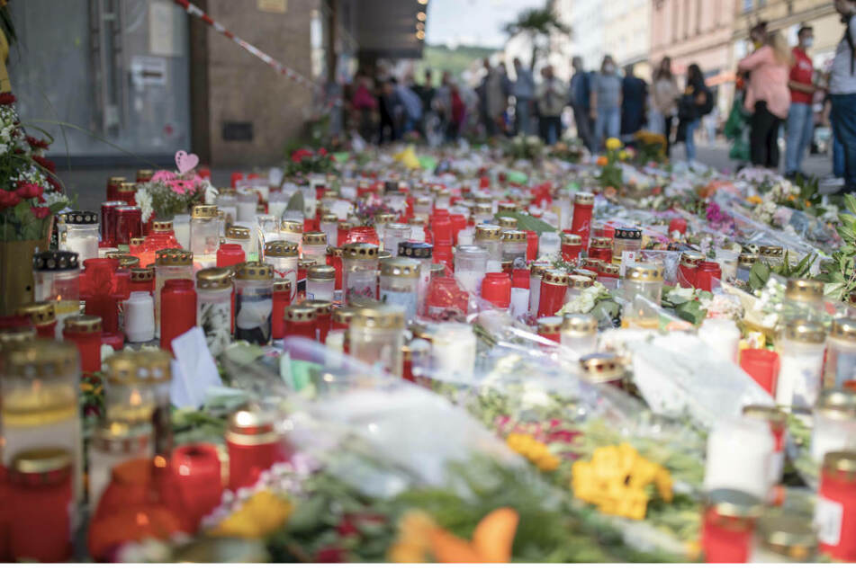 Blumen und Kerzen stehen vor dem Würzburger Kaufhaus, in dem ein 24-jähriger Mann in der vergangenen Woche mehrere Menschen getötet und verletzt hatte.