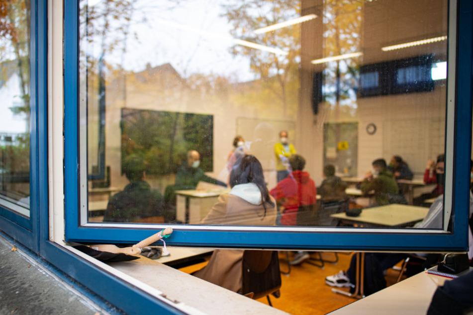 Blick durch das offen stehende Fenster in den Klassenraum einer Schule.
