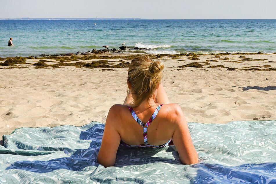 Eine Urlauberin genießt das sommerliche Wetter am Ostseeufer in Timmendorfer Strand. Der weltgrößte Reisekonzern Tui rechnet nach einem weiteren Verlustquartal mit einem schwächeren Sommergeschäft als bislang.