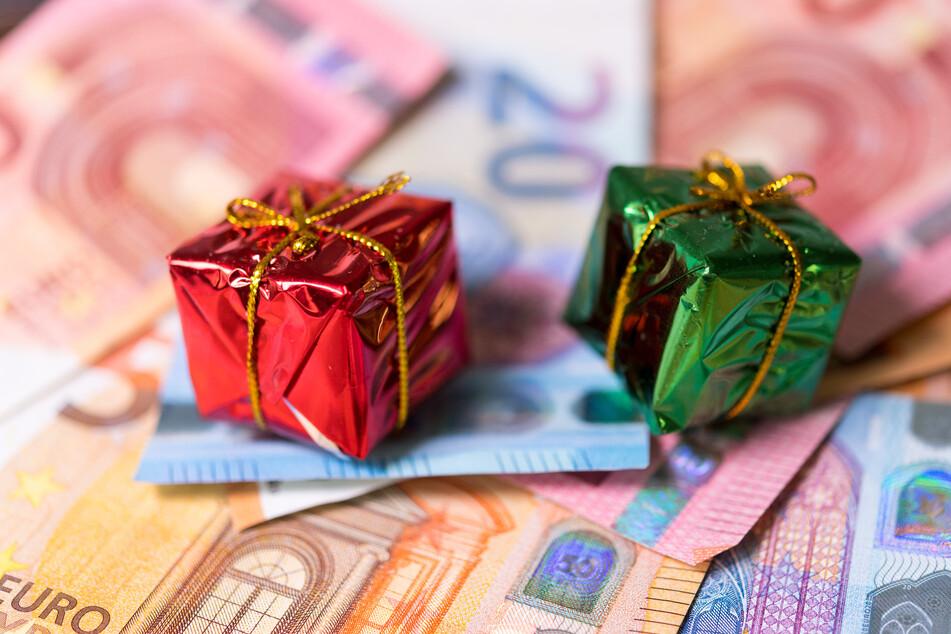 Zwei kleine Geschenke liegen auf zahlreichen Banknoten.