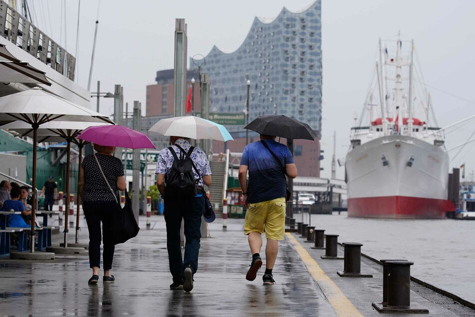 Touristen laufen mit Regenschirmen in der Hand an der Elbpromenade entlang. Im Norden Deutschlands ist es zurzeit sehr regnerisch.