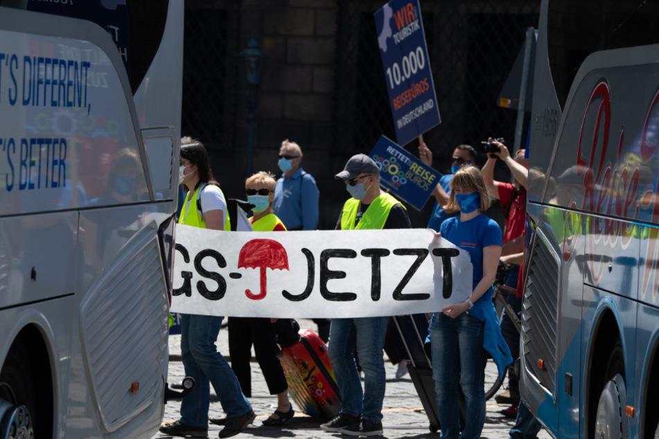"""Teilnehmer einer Demonstration unter dem Motto """"Touristik kurz vor der Ohnmacht"""" gehen auf dem Theaterplatz zwischen Reisebussen entlang."""