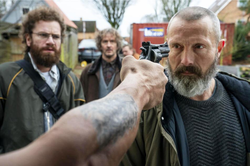 Markus (Mads Mikkelsen, 55, r.) lässt sich auch nicht von einer Pistole im Gesicht aus der Ruhe bringen. Als Soldat hat er dem Tod schließlich oft genug ins Auge geblickt.