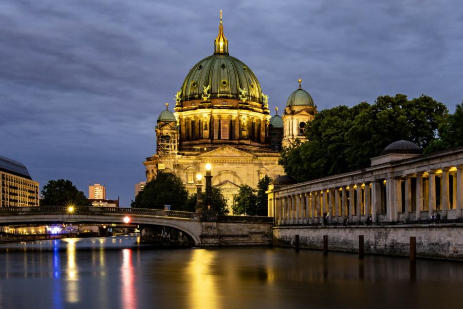 Der Berliner Dom ist am frühen Abend hell erleuchtet.