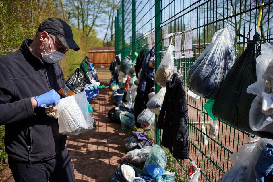 Björn Boueke ordnet an einem sogenannten Gabenzaun die Sachspenden, die Bürger für Wohnungslose an den Zaun eines Bolzplatzes gehängt haben.
