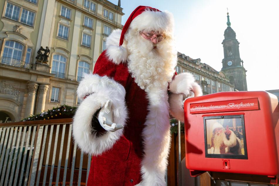 """Weihnachtsmann Steffen Urban (56) kontrolliert regelmäßig den """"Posteingang"""" im roten Wunschzettel-Postkasten auf dem abgesagten Striezelmarkt."""