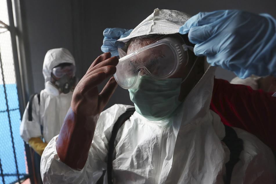 Ein Mitarbeiter des Roten Kreuzes erhält Hilfe beim Anziehen des Schutzanzuges - hier in Indonesien.