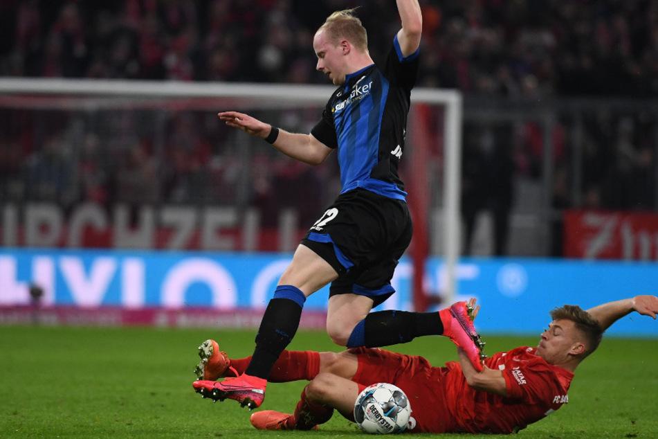 Bayerns Joshua Kimmich (r.) kämpft mit Paderborns Dennis Jastrzembski um den Ball.