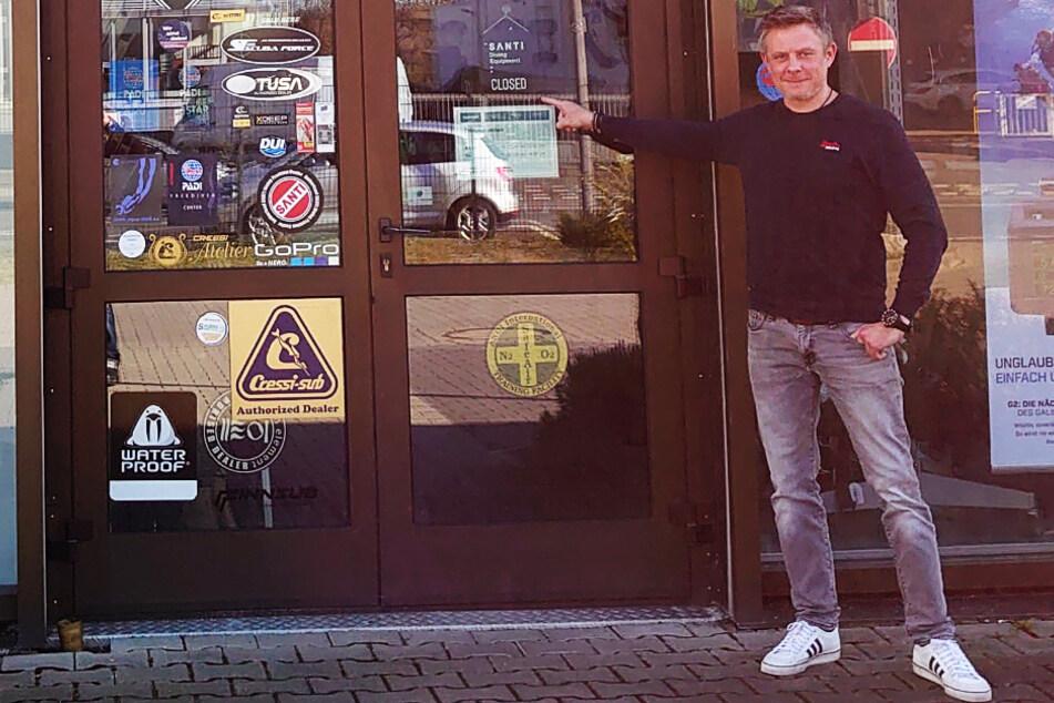 """Heiko Geisen deutet auf das """"Closed""""-Schild an seinem Laden in der Wächtersbacher Straße in Frankfurt"""