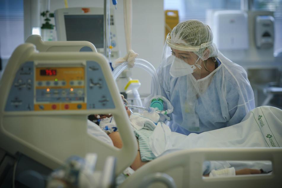 Eine medizinische Mitarbeiterin behandelt einen Covid-19-Patienten auf der Intensivstation.