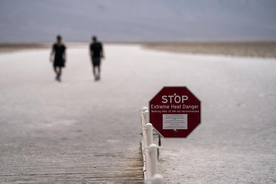 Ein Schild warnt vor extremer Hitze, während Menschen auf den Salzflächen im Badwater Basin spazieren gehen, im Death Valley National Park, Kalifornien.