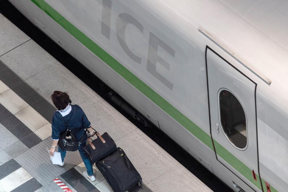 Eine Frau auf einem Bahnsteig auf dem Weg zum Zug.