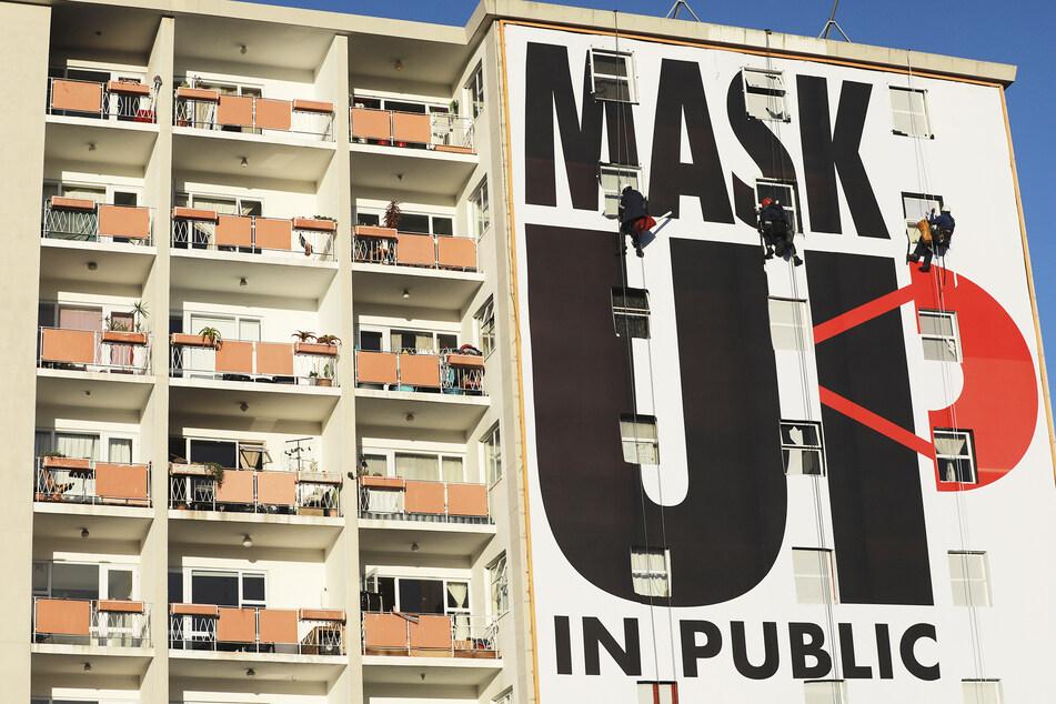 """Arbeiter bringen ein Plakat an einer Hauswand an mit der Aufschrift """"Mask Up in Public"""" (deutsch: Masken auf in der Öffentlichkeit)."""