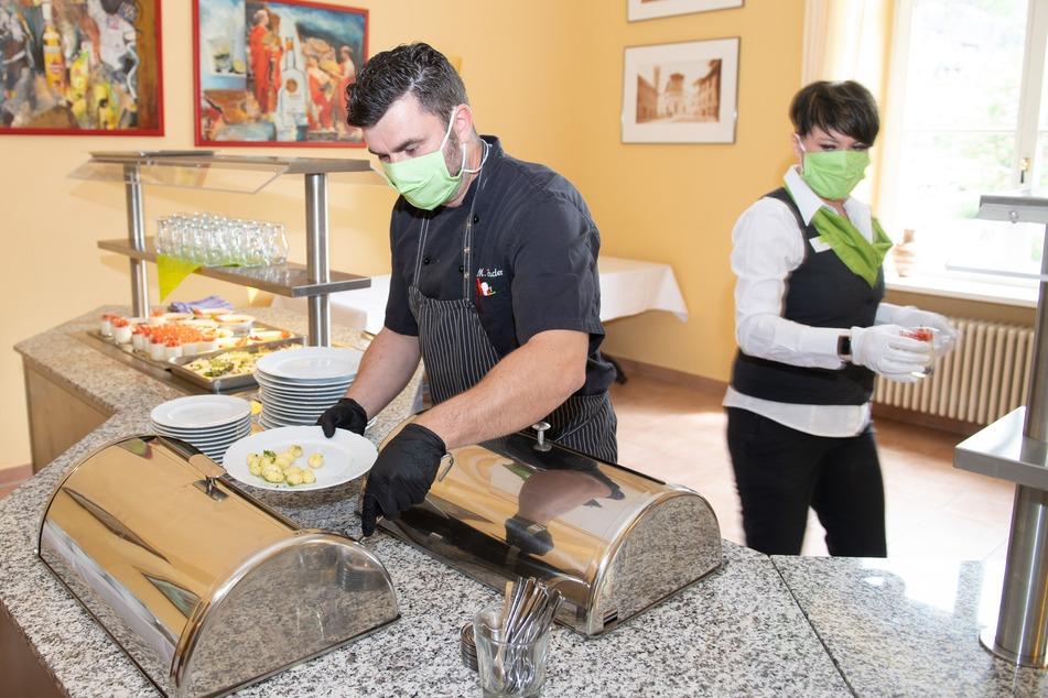 Manuel Enders, Küchenchef, und Mareen Funke, Restaurantleiterin, portionieren im Restaurant des Parkhotel Bad Schandau die Speisen.