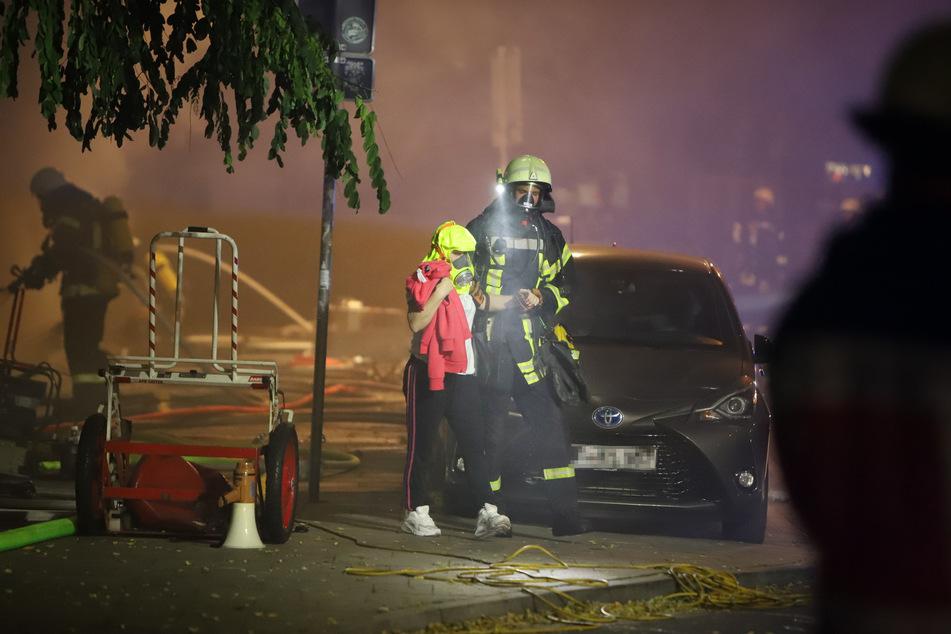 Ein Feuerwehrmann begleitet eine Person, die eine Rettungshaube trägt, von dem brennenden Haus weg.