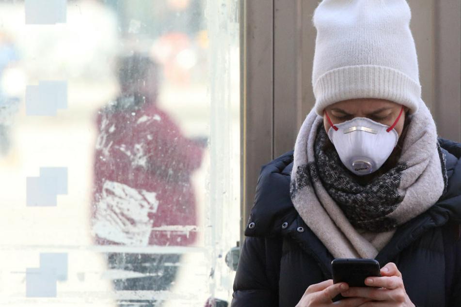 Eine junge Frau mit Schutzmaske informiert sich auf dem Alexanderplatz im Bezirk Mitte mit ihrem Smartphone über die Nachrichtenlage und über die weitere Entwicklung beim Coronavirus.