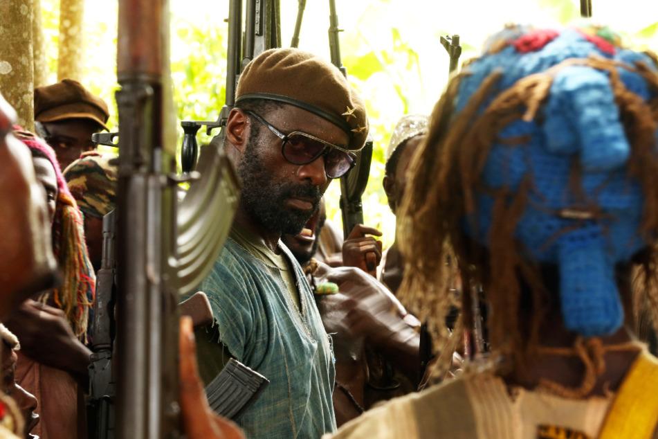 Der Commandant (l., Idris Elba) hat gleich mehrere Kindersoldaten in seinen Reihen, die er grausame Dinge tun lässt.