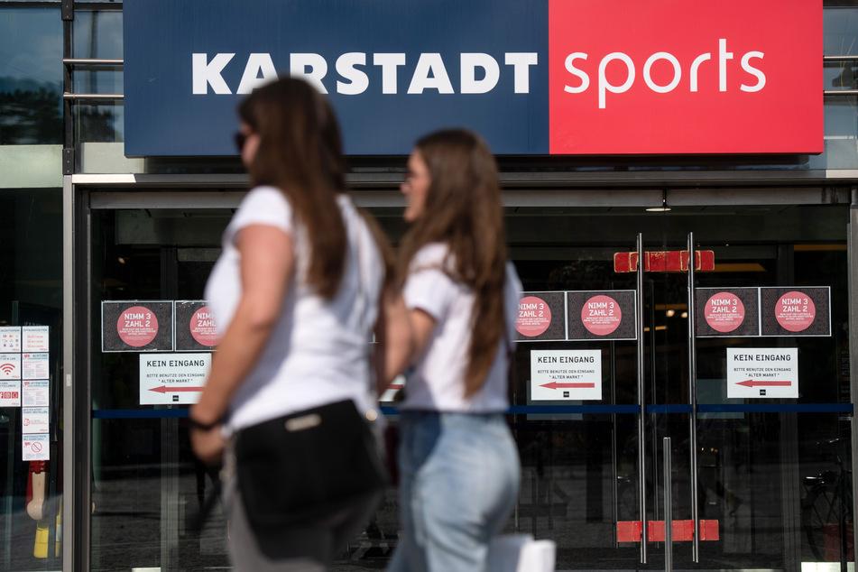 Passanten vor einer Filiale von Karstadt Sports.