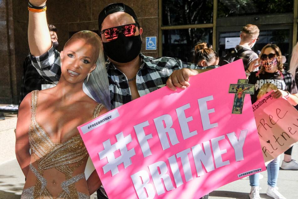 """Ein Fan und Unterstützer von Britney Spears hält bei einer Protestveranstaltung vor dem Stanley Mosk Gerichtsgebäude in Los Angeles neben einem Spears-Pappaufsteller ein Plakat mit der Aufschrift """"#Free Britney""""."""