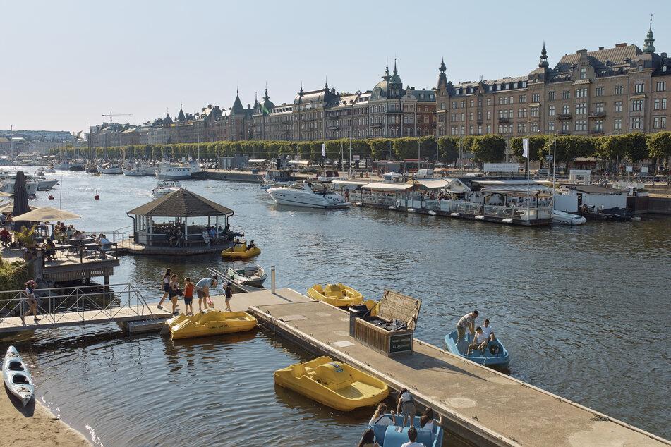 Bei den jährlichen Mittsommerfeierlichkeiten sitzen Menschen in Restaurants und fahren in Tretbooten. Schwedens öffentliche Mittsommerfeiern sind in diesem Jahr verhalten, da große gesellschaftliche Zusammenkünfte aufgrund der andauernden COVID-19-Pandemie verboten sind.