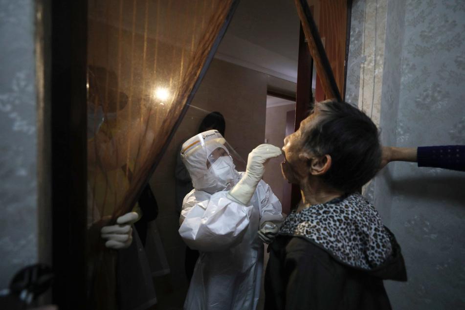Ein medizinischer Mitarbeiter entnimmt einer Frau bei einem Hausbesuchen in Wuhan (China) einen Abstrich für einen Coronavirus-Test. Wuhan gilt als Epizentrum des Corona-Ausbruchs. Trump wirft der WHO schwere Versäumnisse in der Corona-Krise und China-Hörigkeit vor.