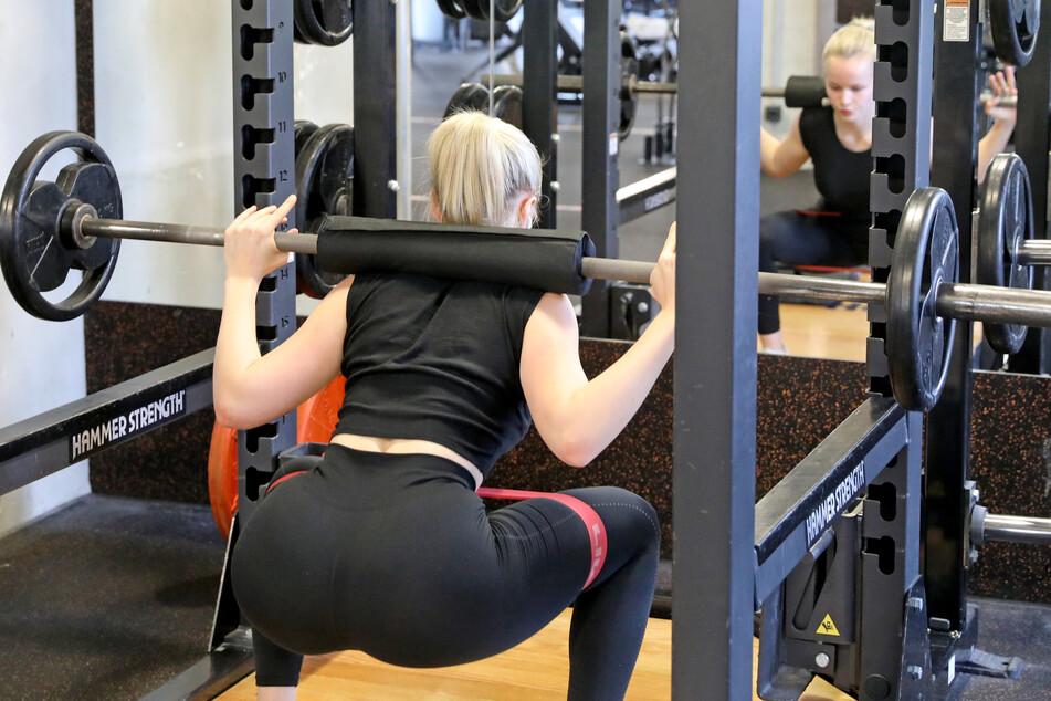 Eine Frau übt Kniebeugen in einem Fitnessstudio aus (Symbolfoto).