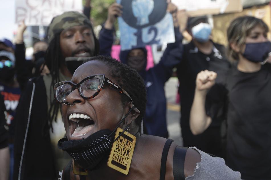 Eine Demonstrantin schreit während Unruhen vor Wut über Rassismus.