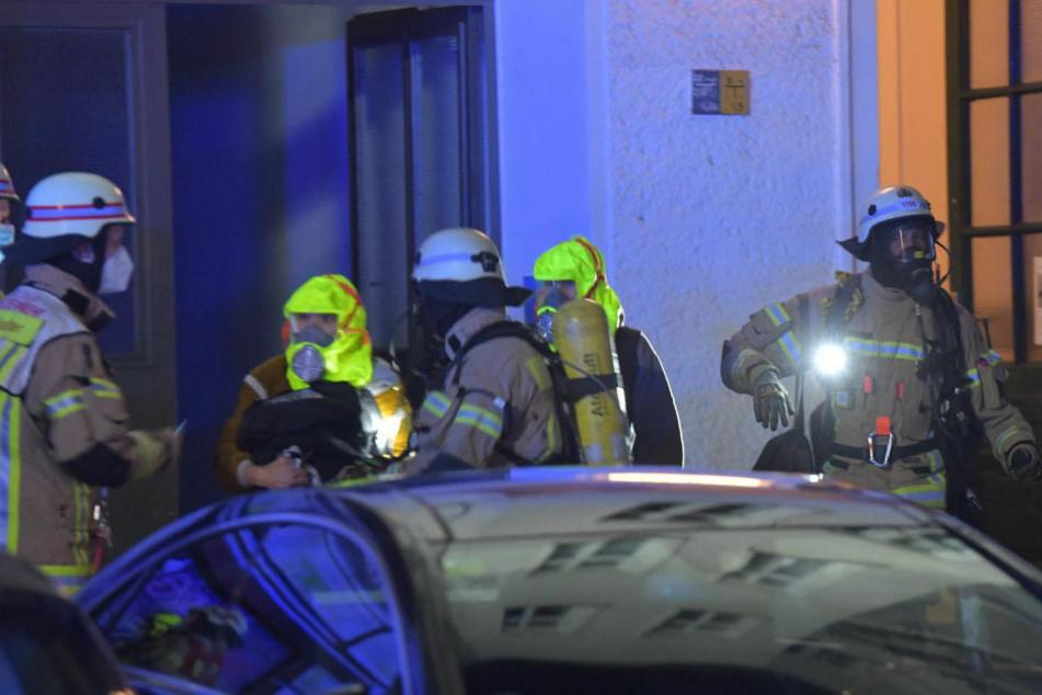 Die Feuerwehrleute bringen zwei gerettete Personen mit Fluchthauben aus dem Haus heraus.