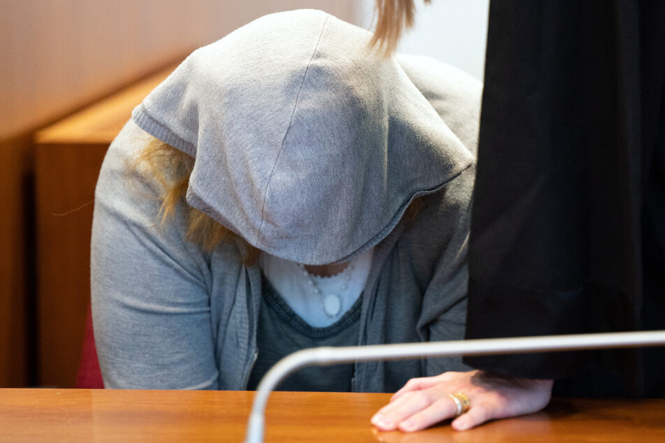 Die 22-jährige Angeklagte sitzt vor Beginn der Verhandlung im Gerichtssaal.