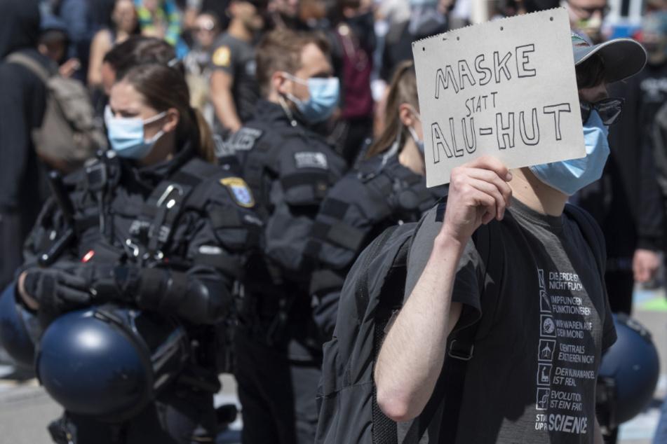Ein Teilnehmer einer Corona-Demo in Frankfurt hält ein Schild hoch.