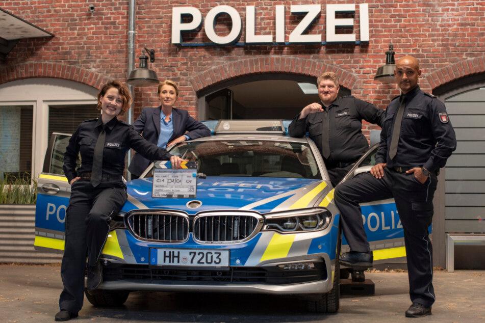 """Wanda Perdelwitz (von links nach rechts), Saskia Fischer, Marc Zwinz und Patrick Abozen posieren zum Drehstart der 34. """"Großstadtrevier""""-Staffel an einem Polizeiauto."""