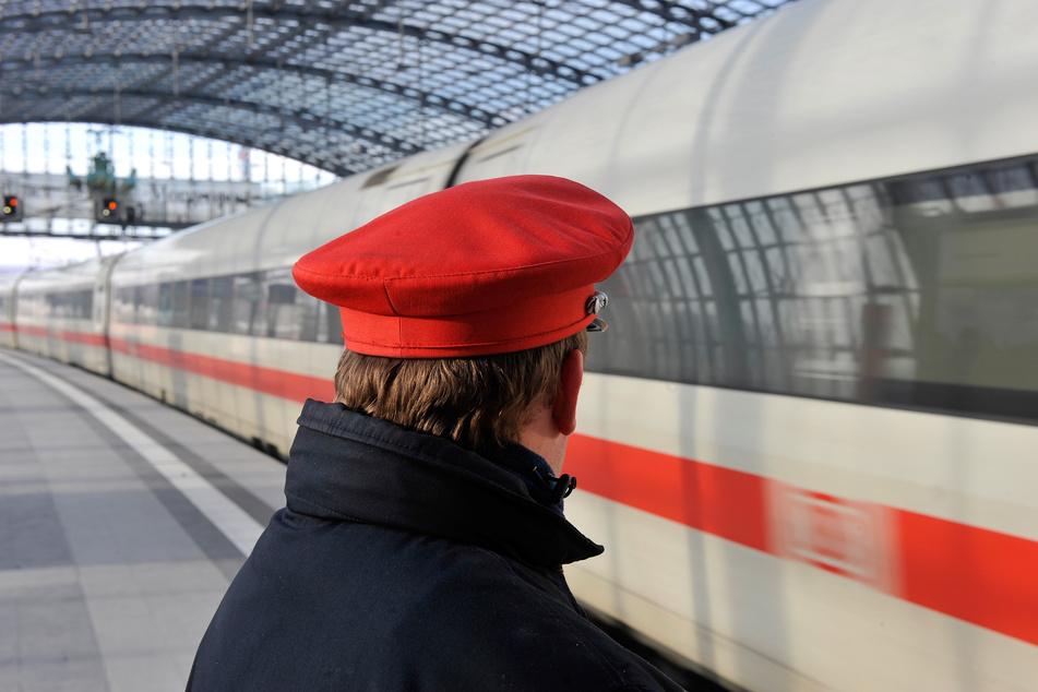 Ein Bahn-Mitarbeiter steht im Berliner Hauptbahnhof am Bahnsteig an einem einfahrenden ICE.