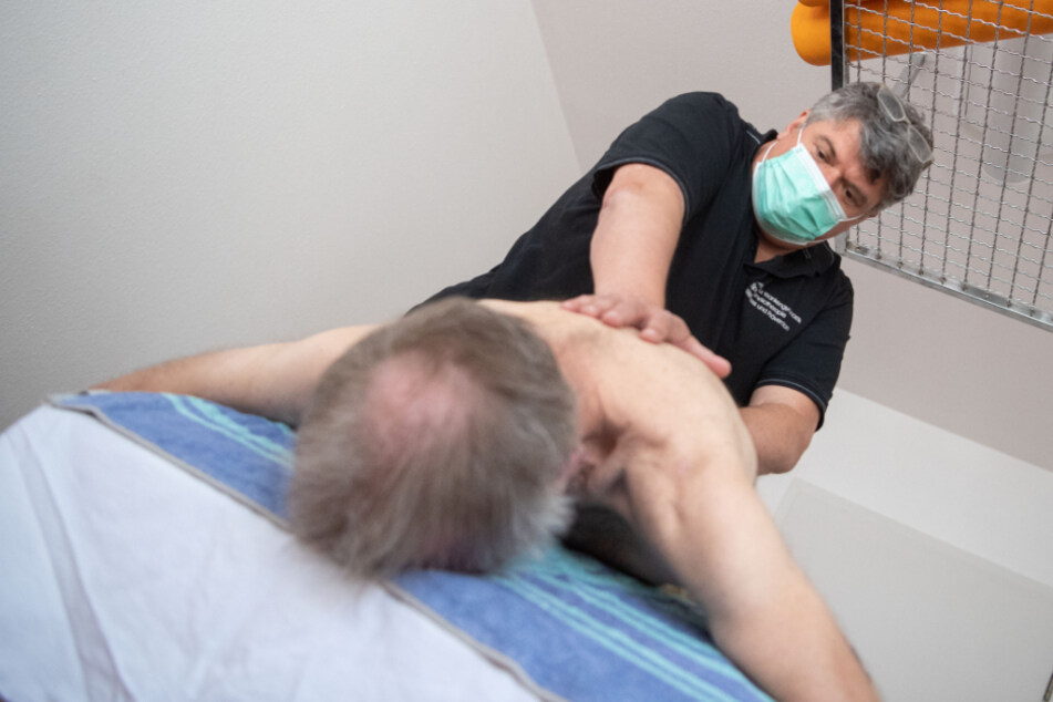 Der Physiotherapeut behandelt einen Patienten.