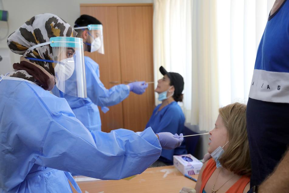 Israelische Mediziner in Schutzkleidung, mit Mundschutz und Schutzschild vor den Gesichtern entnehmen zwei Personen Proben, um sie auf das Coronavirus zu testen.
