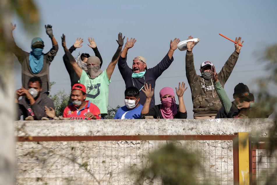 Zum Teil vermummte Demonstranten lachen und rufen Parolen während eines Protests in einem Vorort von Santiago, durch den sie inmitten der Corona-Pandemie Lebensmittel-Hilfen vom Staat forderten.