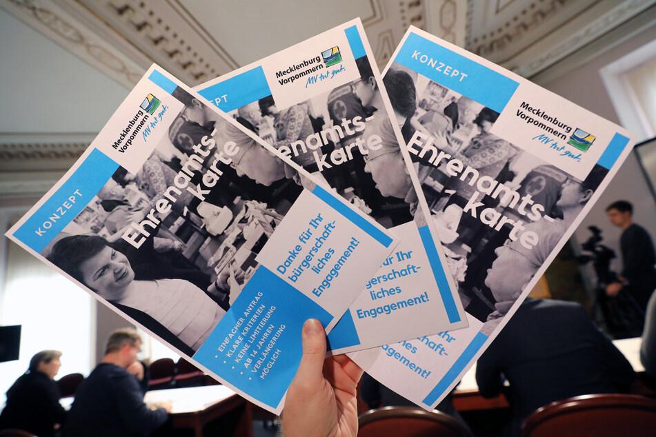 Auf der Landespressekonferenz hält ein Teilnehmer mehrere Blätter mit dem Konzept für die landesweite Ehrenamtskarte in der Hand.