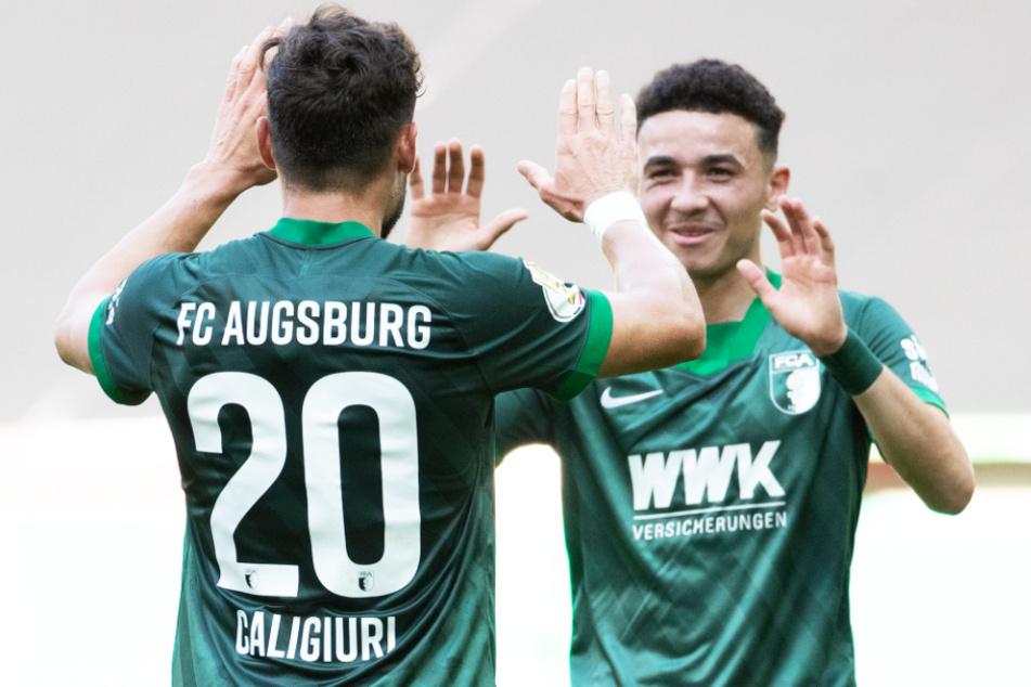 Daniel Caligiuri (l.) und Ruben Vargas haben gute Chancen, den vorzeitigen Klassenerhalt mit dem FC Augsburg zu feiern.
