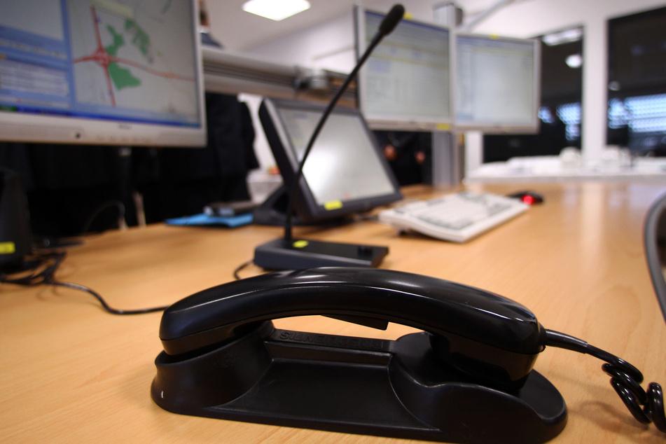 Ein Telefon steht in einer Einsatzleitstelle der Polizei an einem Arbeitsplatz.