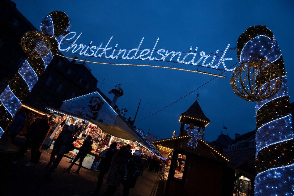"""Das Wort """"Christkindelsmärik"""" prangt in großen beleuchteten Buchstaben an einem Zugang zum Weihnachtsmarkt."""