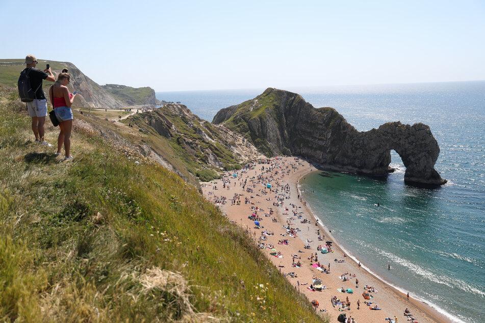 Zahlreiche Menschen halten sich am Strand bei Durdle Door, einer natürlichen Felsbrücke aus Kalkstein, auf, obwohl der Gemeinderat von Dorset den Strand für die Öffentlichkeit geschlossen hat, nachdem sich drei Menschen bei Sprüngen von den Felsen schwer verletzt hatten.