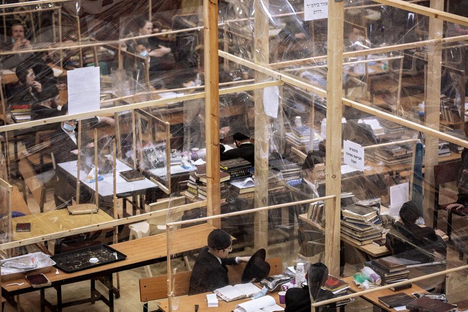 Ultra-orthodoxe jüdische Studenten lesen Texte in einer Jeschiwah, einem jüdischen Priesterseminar, unter Verwendung von Trennwänden aus Plastik. Die Zahl der täglichen Corona-Neuinfektionen ist in Israel erneut gestiegen.
