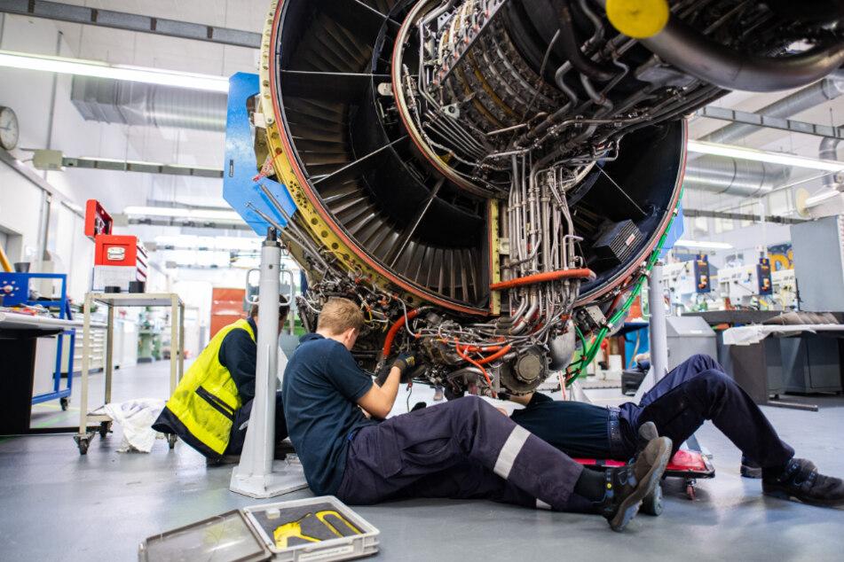 Techniker arbeiten in einer Werkstatt von Lufthansa Technik am Triebwerk eines Flugzeuges. (Archivbild)