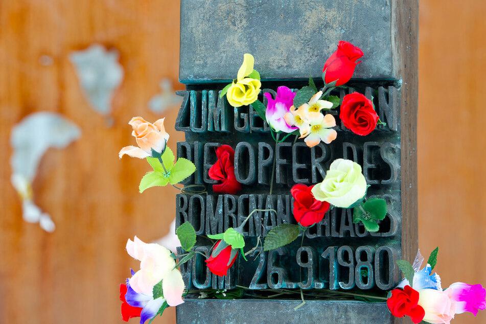 Blumen stecken an einem Denkmal am Haupteingang der Theresienwiese, das an die Opfer des Attentats auf das Oktoberfest erinnert.