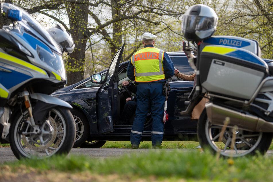 Ein Polizist der Leipziger Verkehrspolizei kontrolliert einen Autofahrer an der Jahnallee in Leipzig.